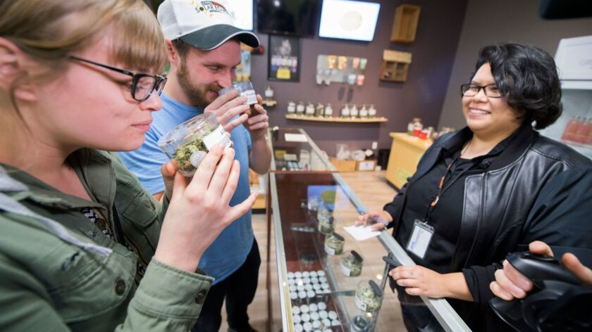Tourists Laura Torgerson and Ryan Sheehan, visiting from Arizona, smell cannabis buds at the Green Pearl Organics dispensary on the first day of legal recreational marijuana sales in California, on Jan. 1, 2018, in Desert Hot Springs.