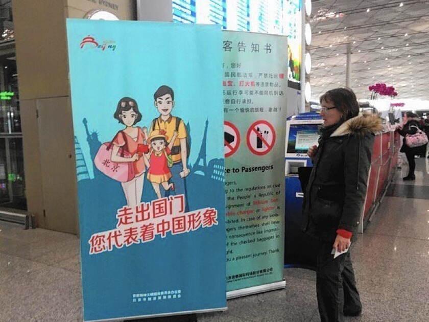 """A sign in Beijing's main airport reminds Chinese to be civilized travelers because they """"represent China's image"""" when they go overseas."""