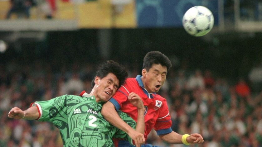 Mexico's Claudio Suarez, left, battles for the ball with South Korea's Kim Do Hon during the South Korea vs. Mexico, Group E, World Cup 98, soccer match at Gerland stadium in Lyon, Saturday, June 13 1998. Mexico defeated South Korea 3-1.