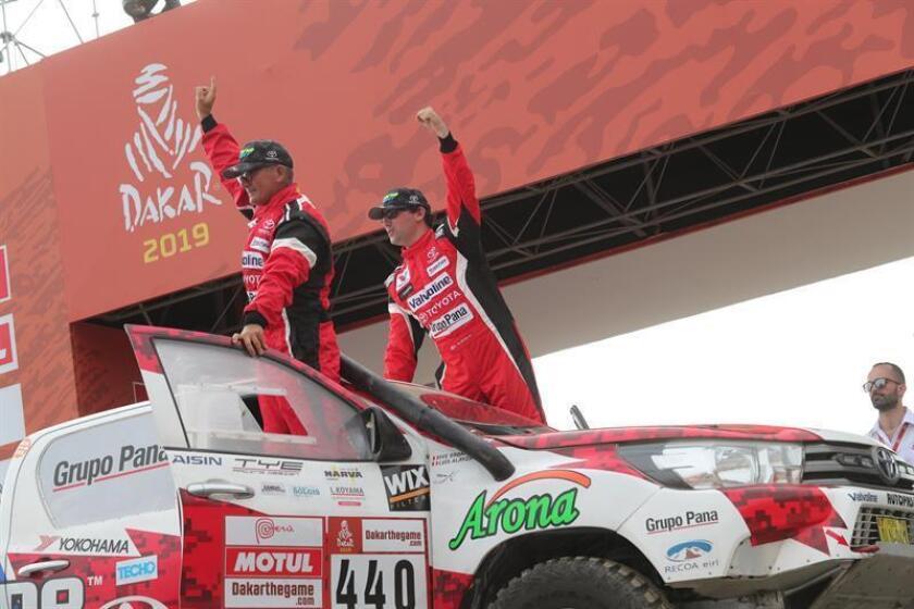 Los peruanos Luis Alayza (c) e Ive Bromberg (i) saludan en el podio de partida del rally Dakar 2019 en la Costa Verde en Lima (Perú). EFE/Archivo