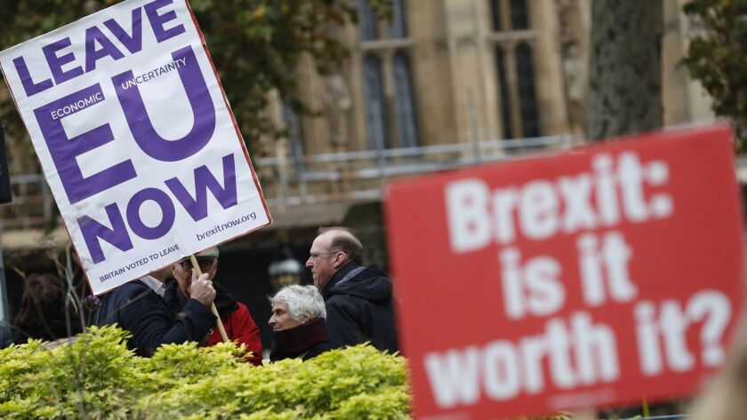 Pro and anti Brexit protesters hold placards as they vie for media attention near Parliament in Lond