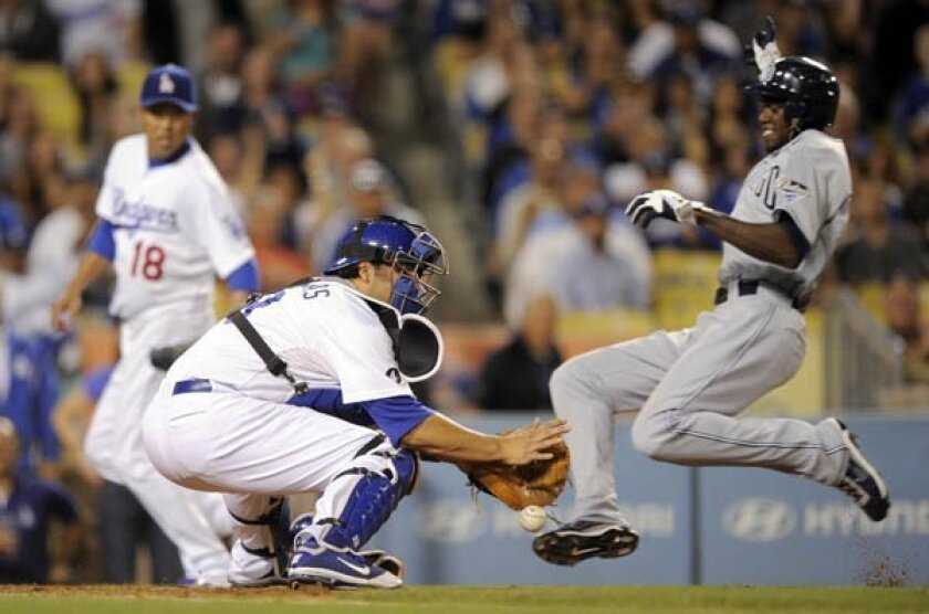 Cameron Maybin scores on a sacrifice fly by Tim Stauffer as Los Angeles Dodgers catcher Rod Barajas drops the ball while starting pitcher Hiroki Kuroda, left, looks on during the fifth inning
