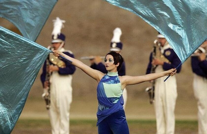 El Camino High School band auxilliary member Elizabeth Doyle twirls the flags during a performance.