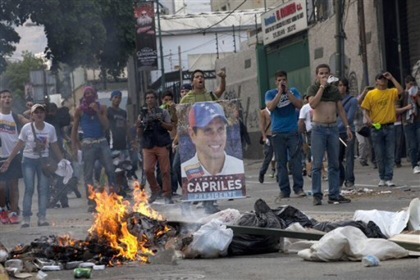 Demonstrators, one holding a poster of opposition presidential candidate Henrique Capriles, confront riot police from behind a burning barricade in the Altamira neighborhood in Caracas, Venezuela, Monday, April 15, 2013. National Guard troops fired tear gas and plastic bullets to disperse demonstra