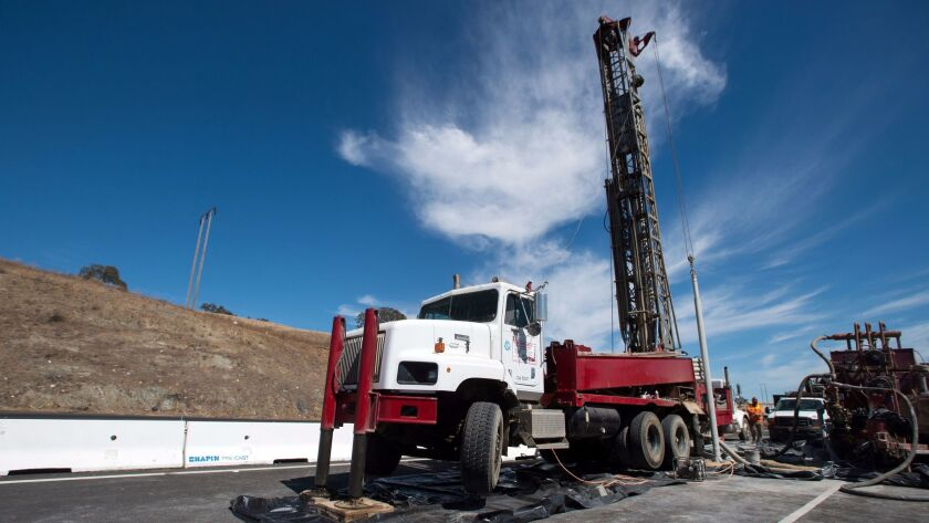 Workers operate a drill rig while testing rock chip samples along the Pacheco Pass in Hollister in September. The California High-Speed Rail Authority is doing geological drilling in preparation for a mile-long tunnel expected to be built for the state's high-speed rail project.