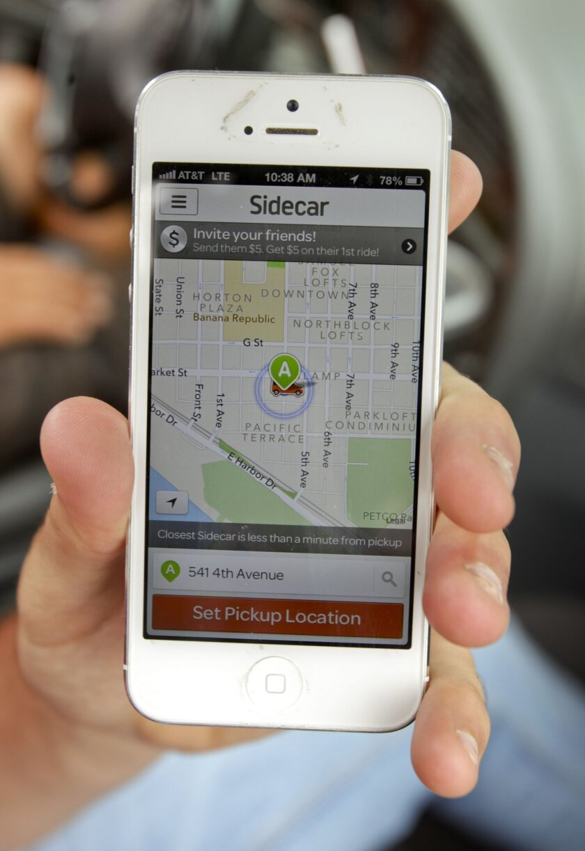 A Sidecar rider shows the ridesharing company's app in downtown San Diego. The app connects people who need rides with those willing to drive them.| Photo Hayne Palmour IV U-T San Diego