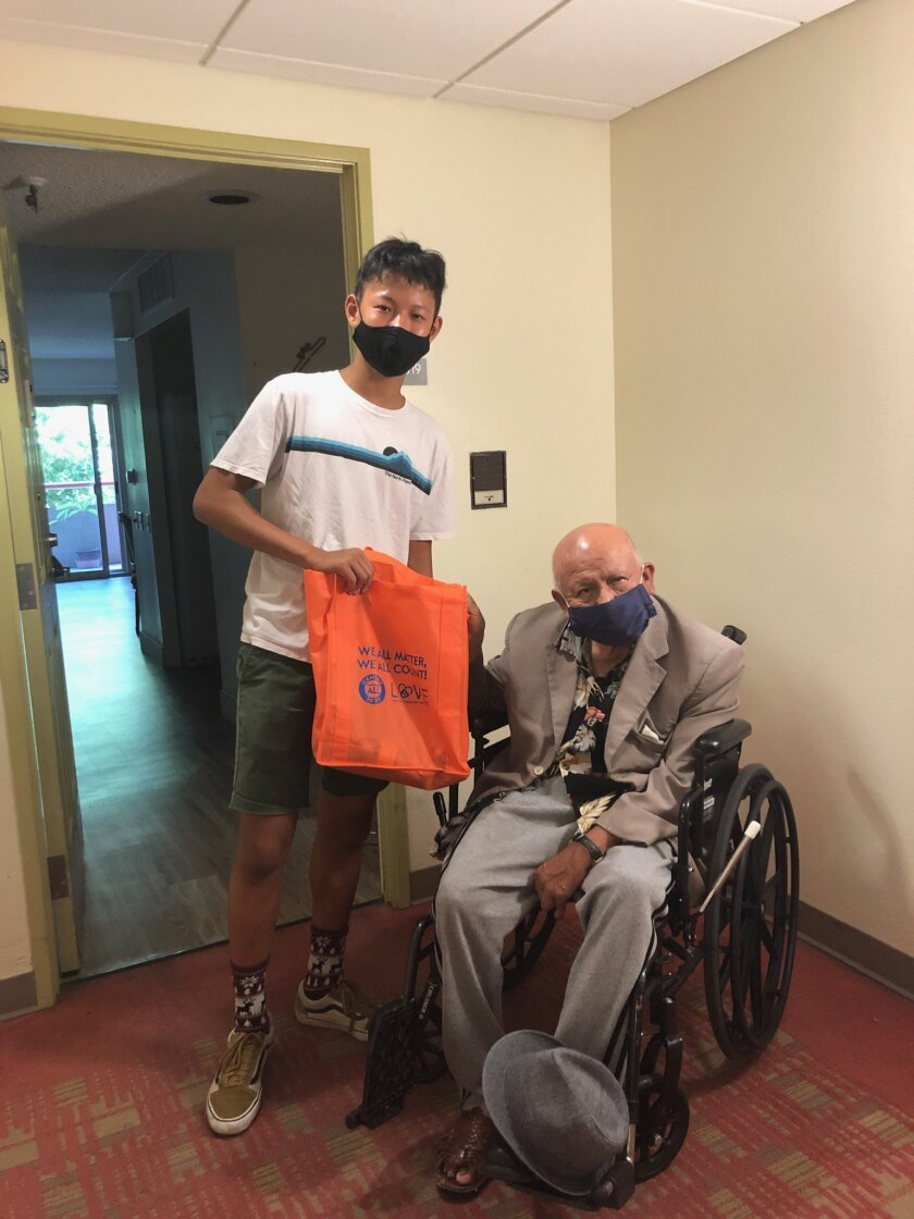 A community volunteer with AASCSC delivers gifts to a senior father.