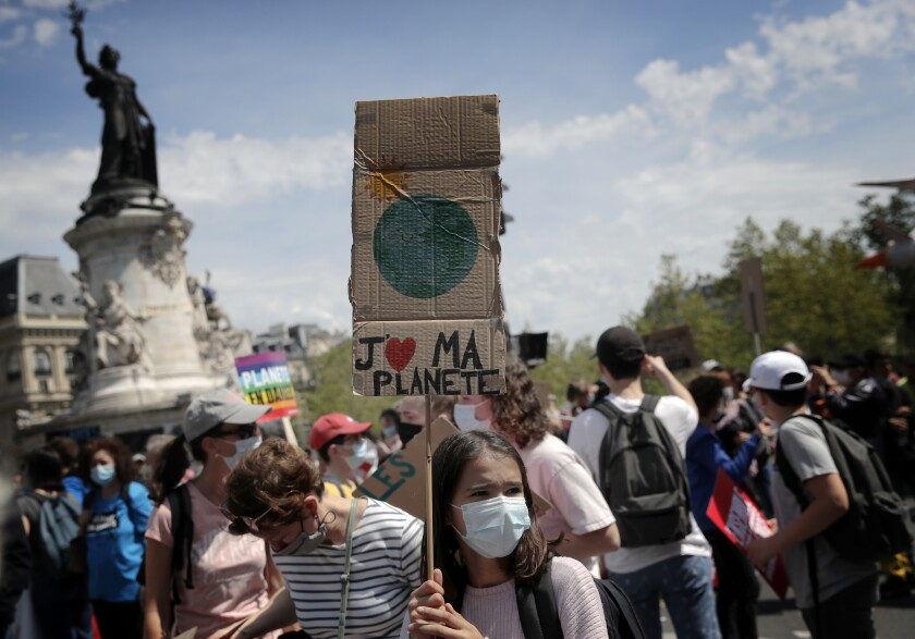 """Una joven sostiene un letrero con la frase """"Amo a mi planeta"""" en francés, durante una protesta contra el cambio climático en París, el domingo 9 de mayo de 2021. (AP Foto/Christophe Ena)"""