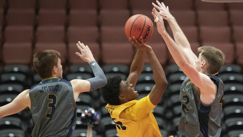 Long Beach State guard Deishuan Booker, center, shoots between UC Irvine guard Robert Cartwright, left, and forward Tommy Rutherford during the first half at the Big West men's tournament in Anaheim on Friday.