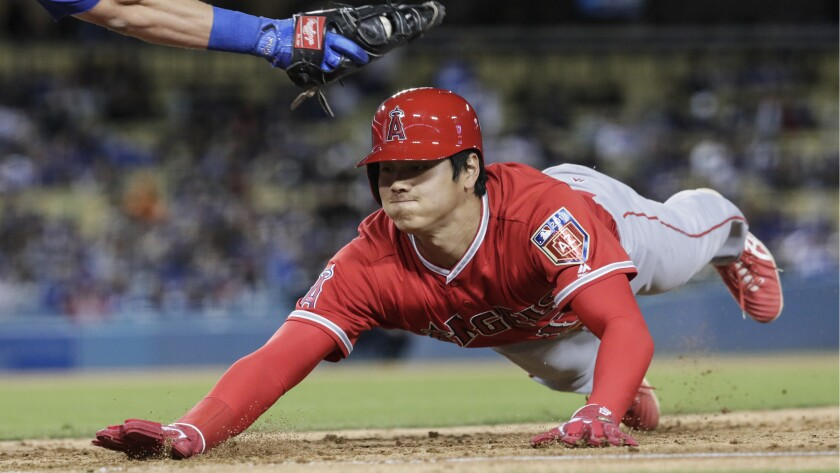 Angels designated hitter Shohei Ohtani dives under the tag of Dodgers first baseman Cody Bellinger on a fourth inning pickoff attempt by pitcher Rich Hill on March 26.