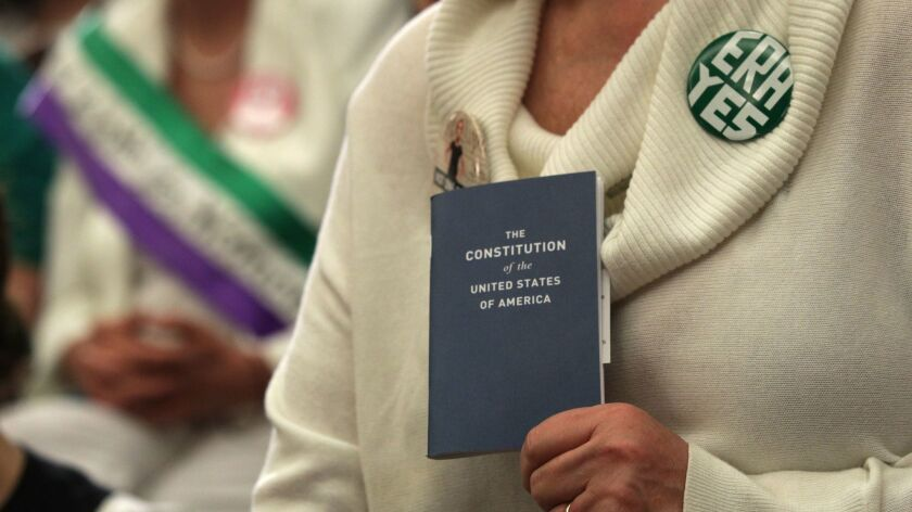 An advocate for ratification of the Equal Rights Amendment holds a copy of the U.S. Constitution