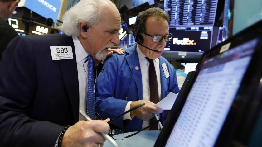 Traders Peter Tuchman, left, and Sal Suarino work on the floor of the New York Stock Exchange on Wednesday.