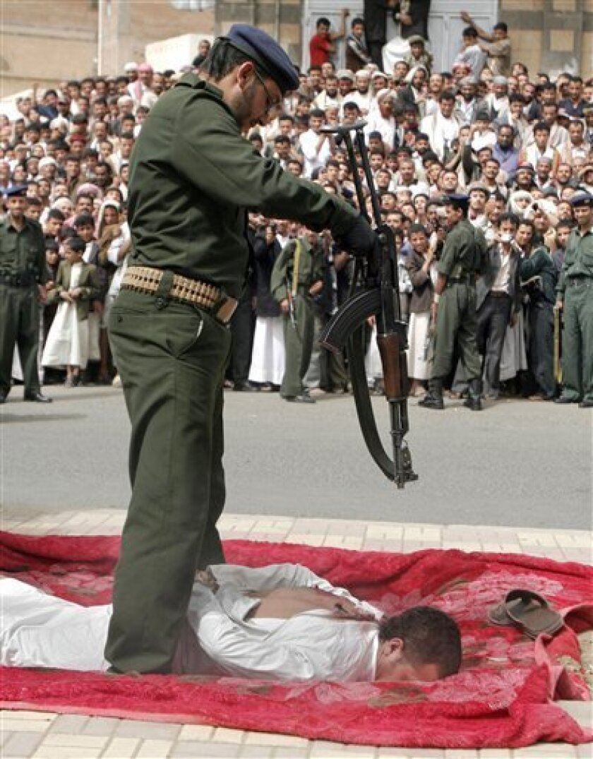Yemenis gather to watch a Yemeni soldier execute a man, lying face down on a large piece of red cloth, his hands bound behind him, in front of the central prison in San'a, Yemen, Monday, July 6, 2009. The Yemen news agency reports that a barber has been publicly executed after he was found guilty of raping and killing an 11-year-old boy who came to his shop for a haircut. According to the news agency, SAB'A, the barber was arrested in December 2008 and confessed during a January trial to raping the boy inside his salon, killing him and cutting his body to pieces before dumping it outside San'a. (AP photo)