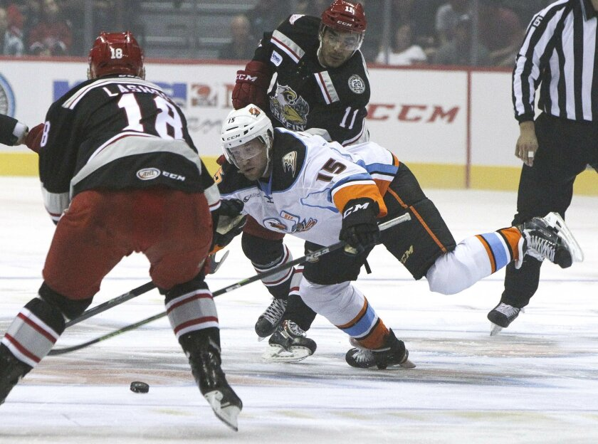 The Gulls' Chris Mueller, right, and Grand Rapids' Brian Lashoff go for the puck in the first period in a game earlier this season.