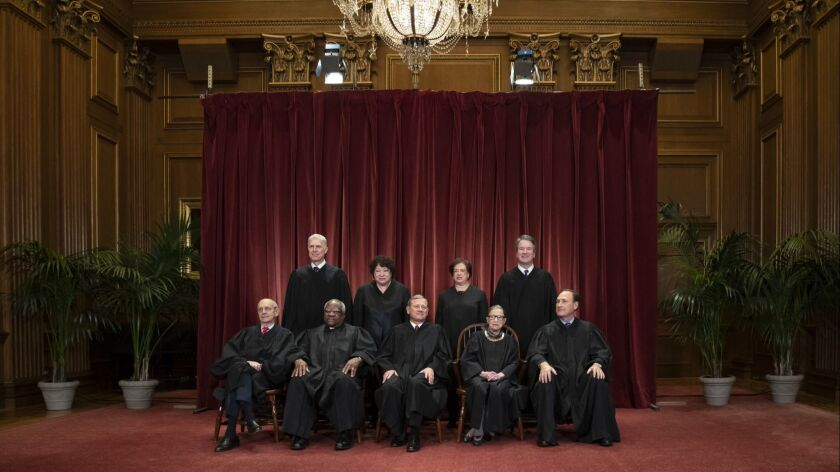 The justices gather for a formal group portrait at the Supreme Court Building in Washington on Nov. 30.