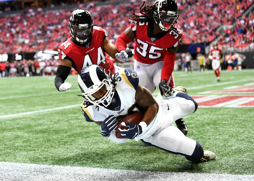 Rams running back Todd Gurley catches a touchdown pass in front of Falcons linebacker  Vic Beasley Jr., left, and safety Jamal Carter.