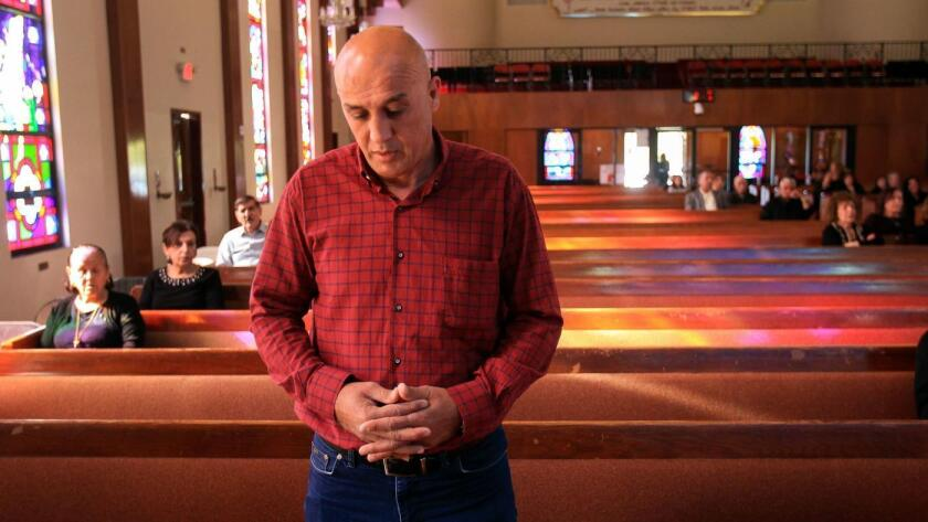 Raied Aqrawi prays before Good Friday services at St. Peter's Chaldean Catholic Church in El Cajon.