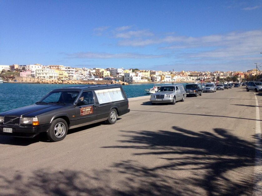 A line of hearses arrive at Lampedusa Harbor in Italy on Feb. 11 as the bodies of migrants who died attempt to cross the Mediterranean from Libya are unloaded from an Italian ship.