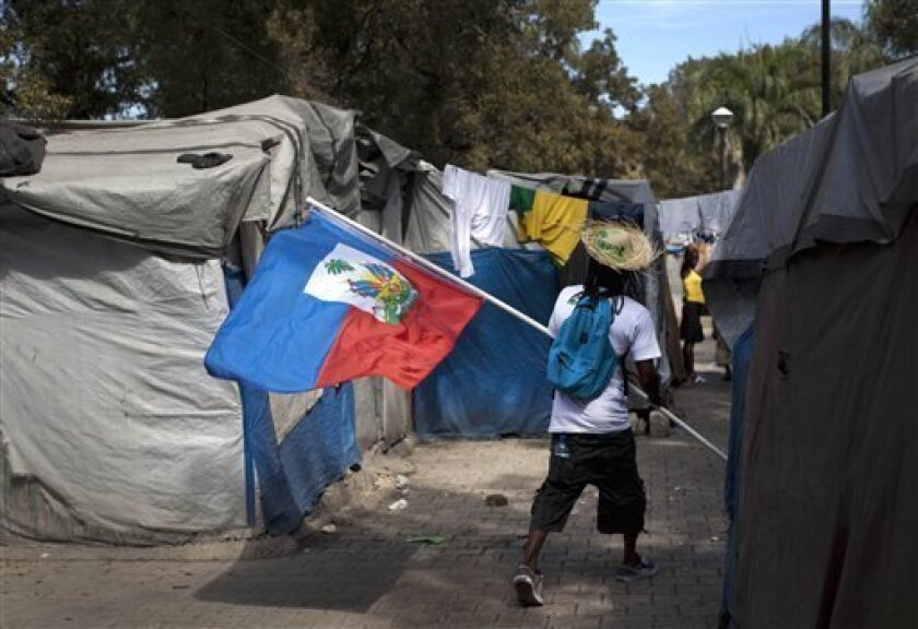 A demonstrator carrying a Haitian flag walks through the Champ de Mars camp, across the street from the collapsed National Palace, during a protest to demand new housing, in Port-au-Prince, Haiti, Wednesday Jan. 11, 2012. Two years after the earthquake and with the help of Canada's government, nearly 20,000 people will be relocated to homes north of the capital, Haiti's President Michel Martelly announced Wednesday. (AP Photo/Ramon Espinosa)