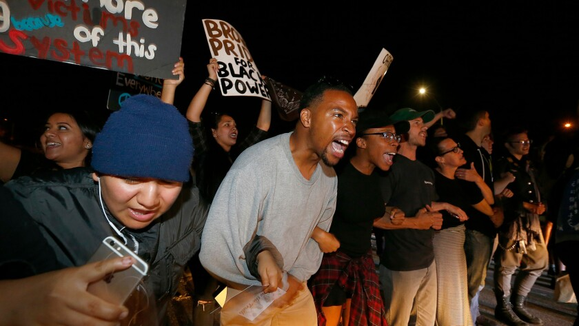 Protesters in support of Black Lives Matter lock arms and chant as they block traffic on the 405 Freeway in Inglewood on Sunday night.