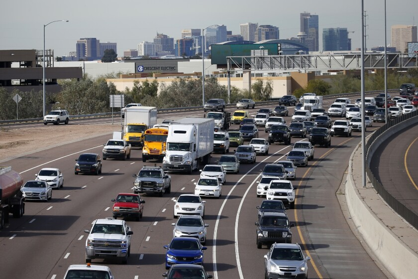 Cars stuck in traffic on a freeway with a city skyline in the background