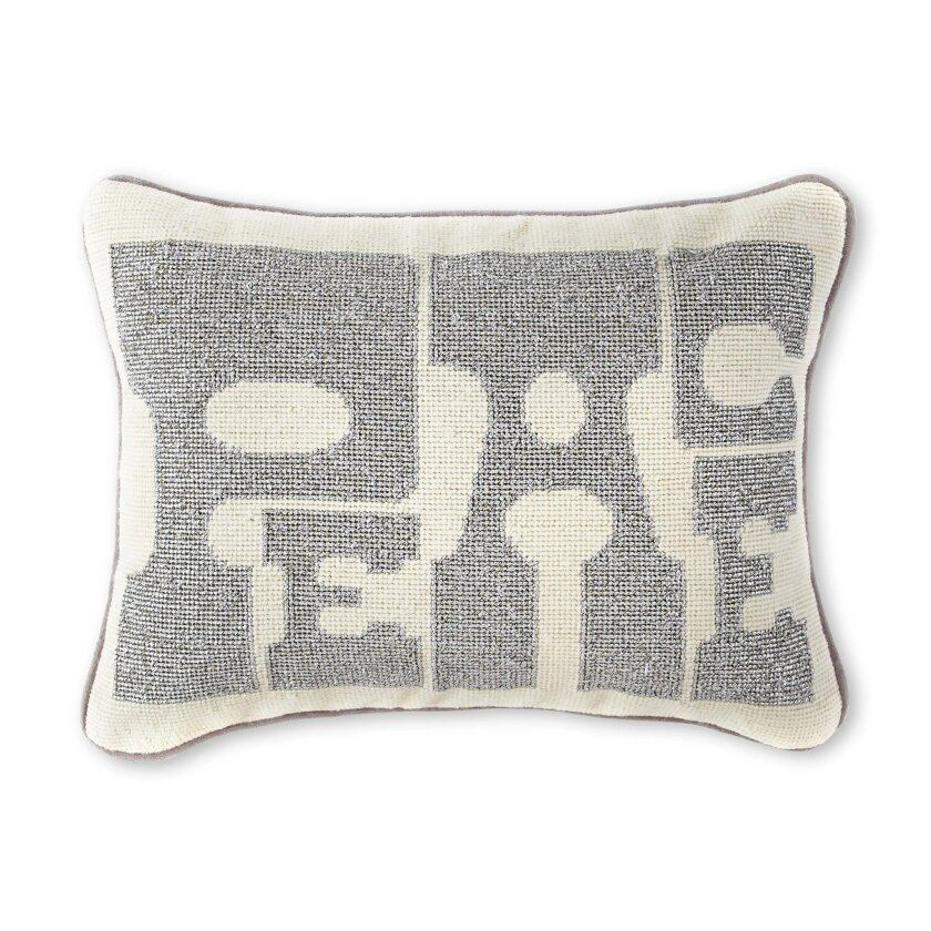In this photo provided by JCPenney, Jonathan Adler's needlepointed Peace pillow adds a holiday message in a hip way. Following the general trend in home decor, holiday trim and accessories this year are a mix of eclectic and traditional colors and styles. Style watchers say we're approaching the ho