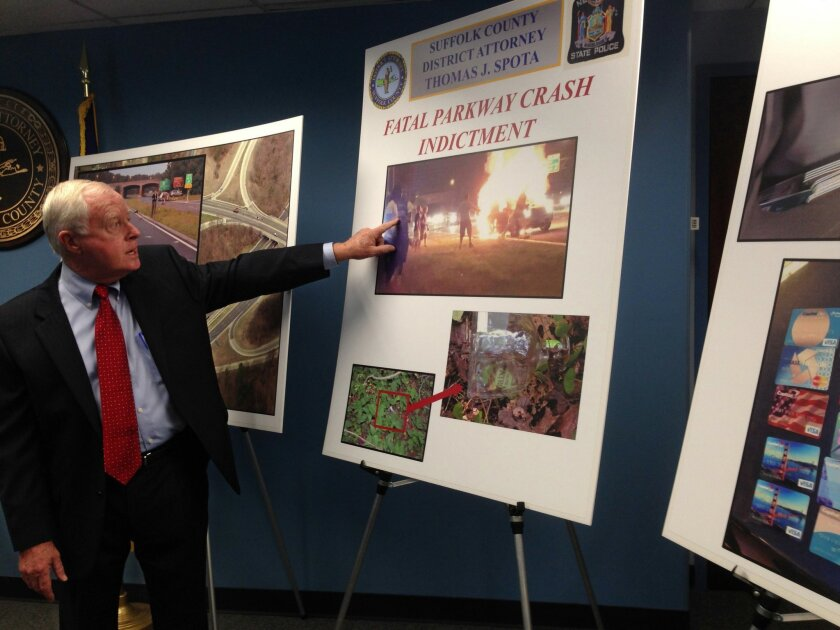 FILE- In this Aug. 27, 2015 file photo, Suffolk County District Attorney Thomas J. Spota points to a photograph of the aftermath of a deadly automobile accident on New York's Long Island, during a news conference in Happague, N.Y. In the prosecution of the man charged with the accident, the Distric