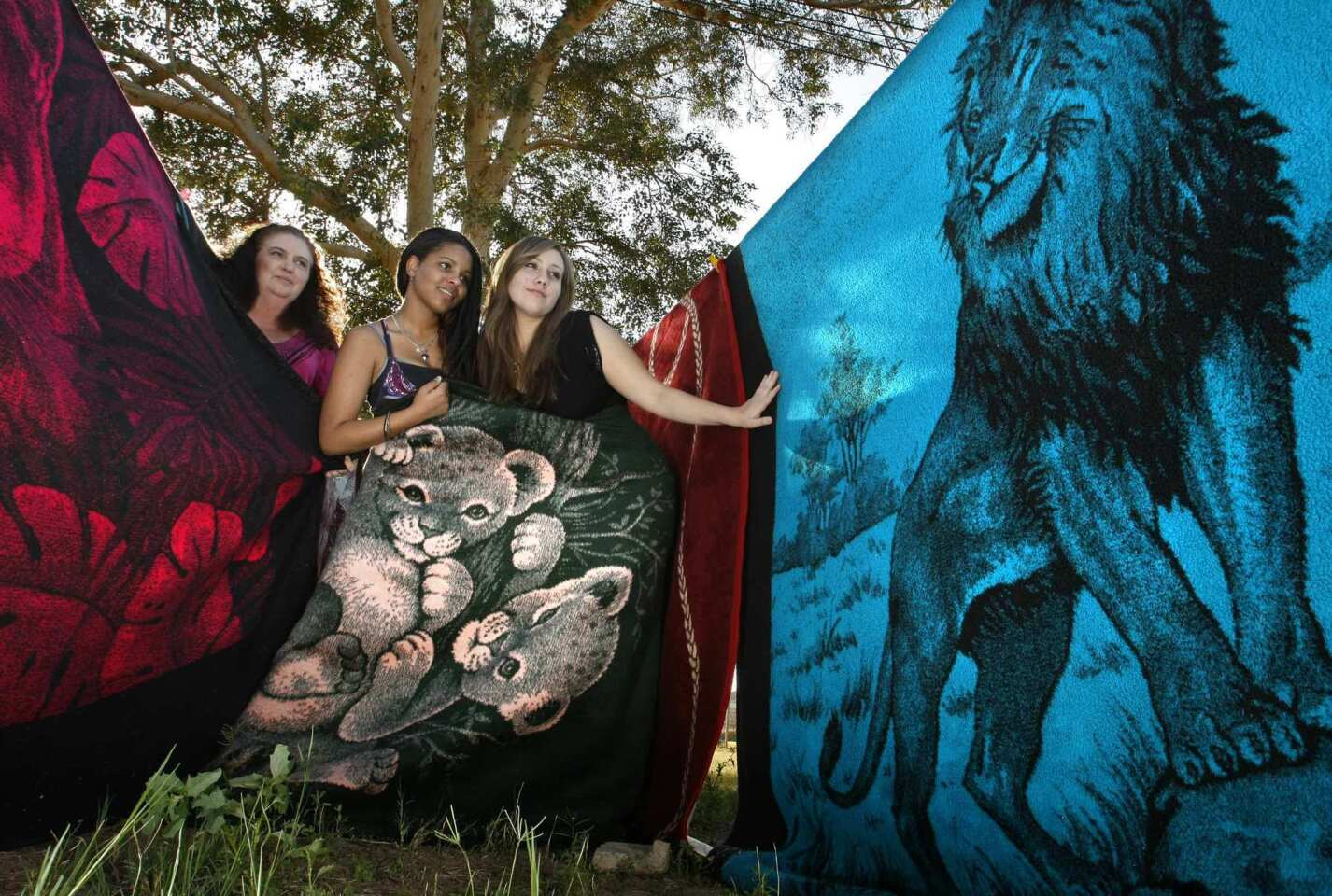 """Paula Valenzuela, left, ended up accumulating almost 400 San Marcos blankets. The El Centro resident and her teenage daughters, Elizabeth, middle, and Mariana, show a few left from Valenzuela's collection. She sold the rest on line after her husband threatened to call the """"Hoarders"""" television show."""