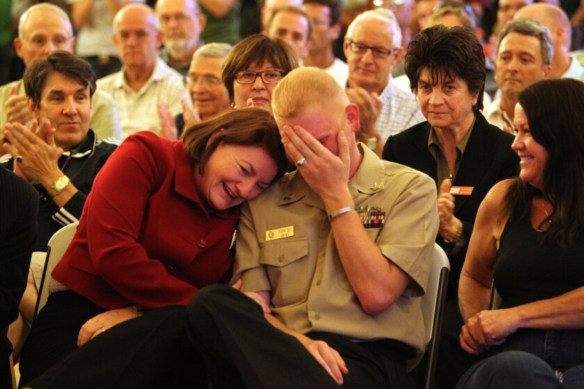 Benjamin Jett, a first class petty officer in the US Navy, can't hold back the tears as he listens to speakers tell their stories of being gay in the military. To the left is Assemblywoman Tori Atkins.