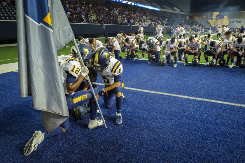 El Paso Eastwood players kneel in prayer before a high school football game against Plano on Sept. 5 in Frisco, Texas.
