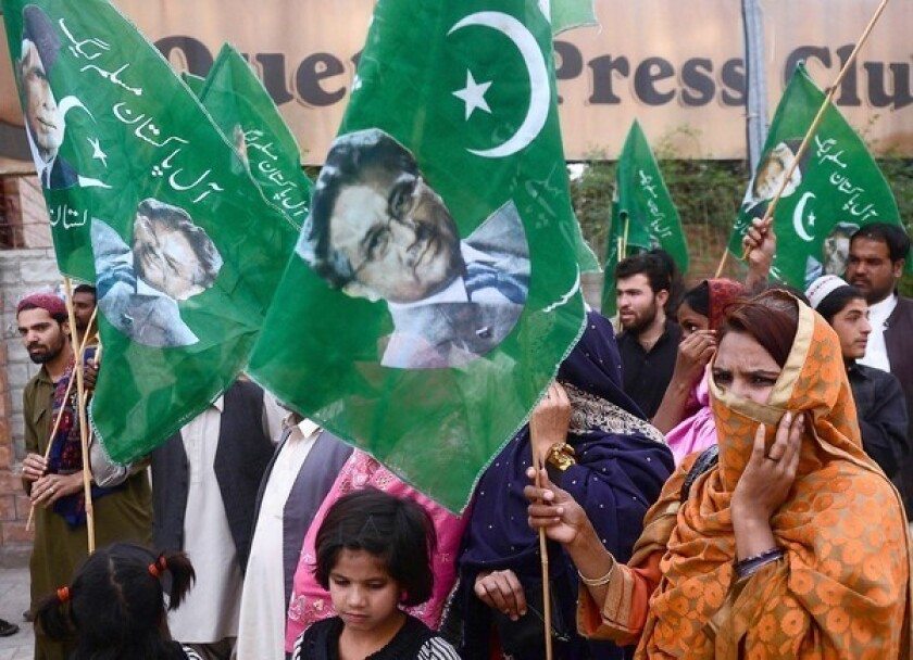 Supporters of former Pakistani military ruler Pervez Musharraf carry party flags during a rally April 19 in Quetta, Pakistan. The former president was in police custody after being arrested early Friday.