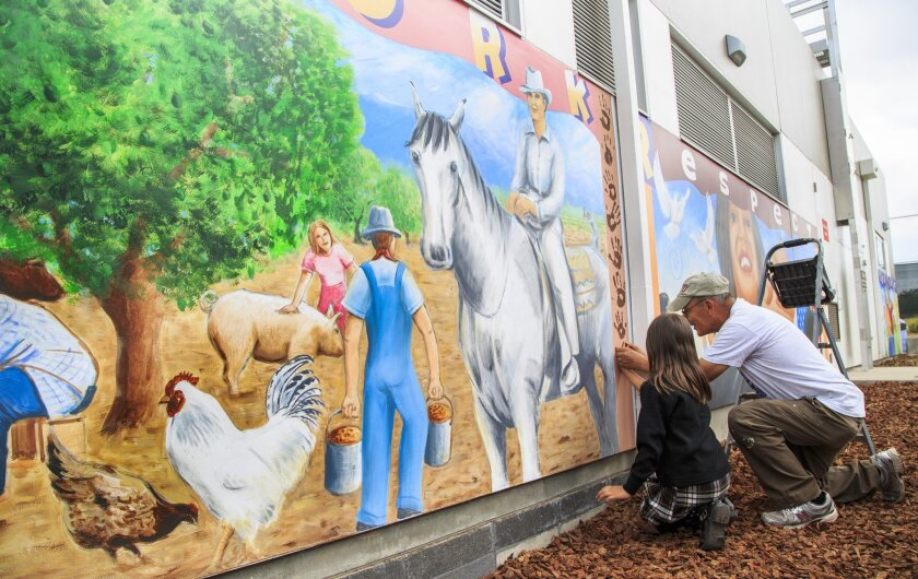Local artist Salvador Barajas helps Alina Moreno leave her hand print on a mural at the Lincoln Acres Library in National City.