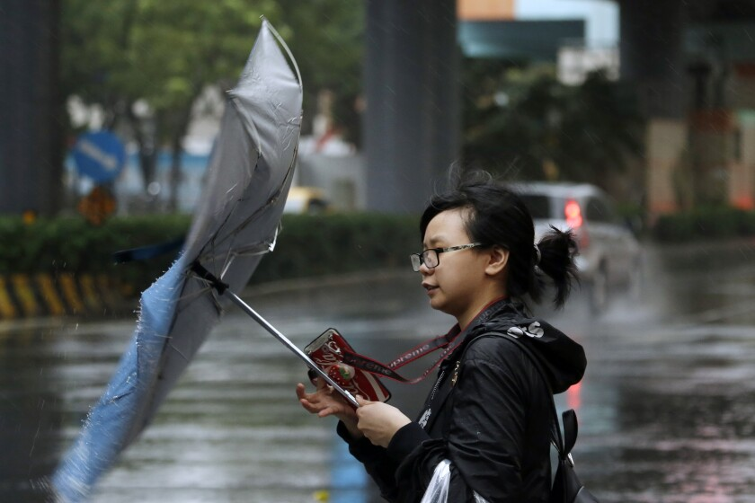 A woman struggles against gusts of wind generated by Typhoon Mitag in Taipei, Taiwan, Monday, Sept. 30, 2019. Fast-moving Typhoon Mitag was bearing down on northern Taiwan on Monday, bringing high winds and heavy rain and forcing flight cancellations. (AP Photo/Chiang Ying-ying)