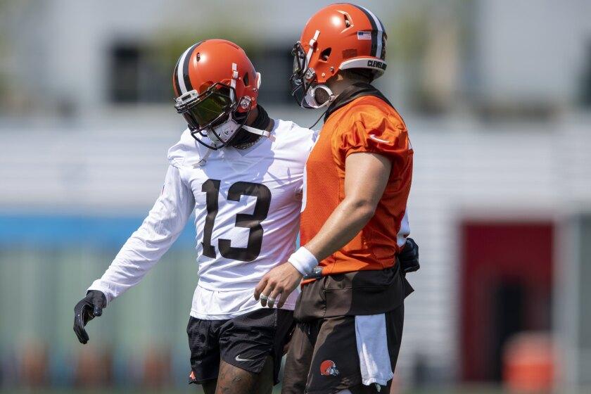 Cleveland Brows wide receiver Odell Beckham Jr., left, hugs quarterback Baker Mayfield (6) during NFL football practice in Berea, Ohio, Wednesday, July 28, 2021. (AP Photo/David Dermer)