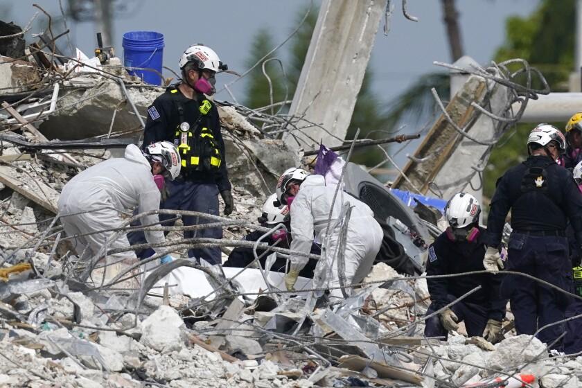 Rescue handling tarp in condo tower rubble