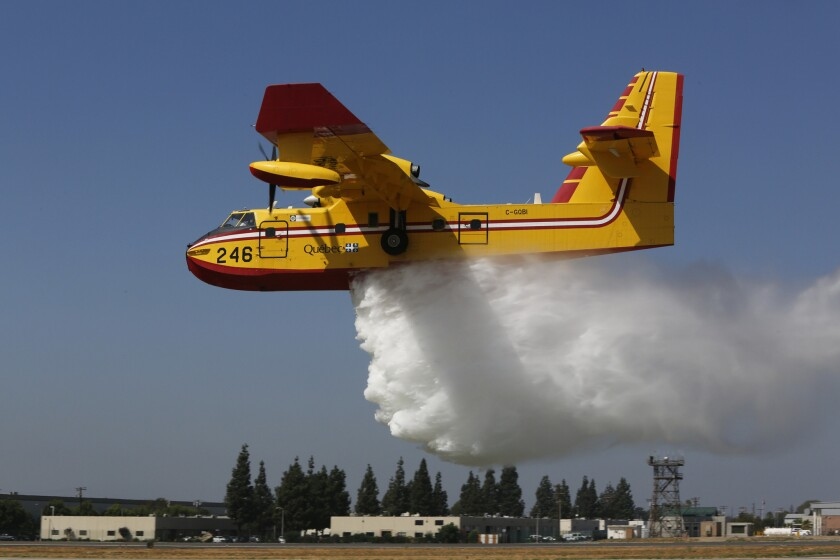 """""""Super scooper"""" Quebec 1 makes a water drop on the grass next to the runway at the Van Nuys Airport on Wednesday."""