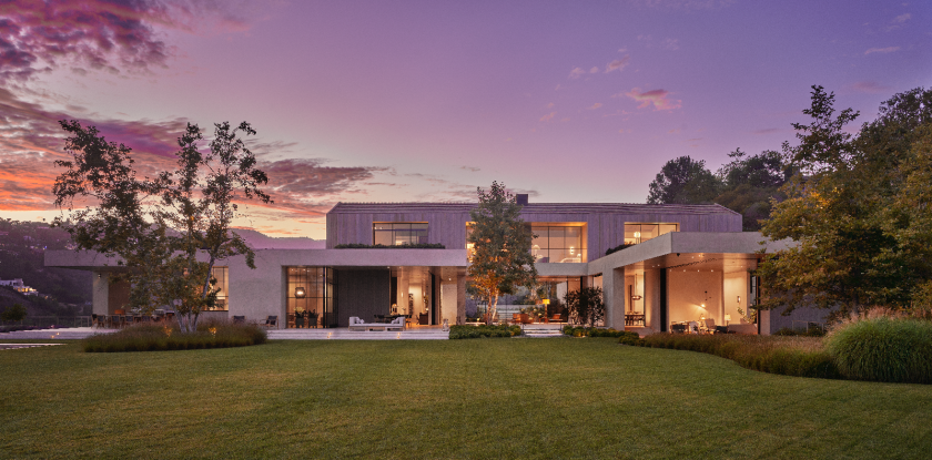 The exterior of a sleek, two-story modern mansion with large windows.