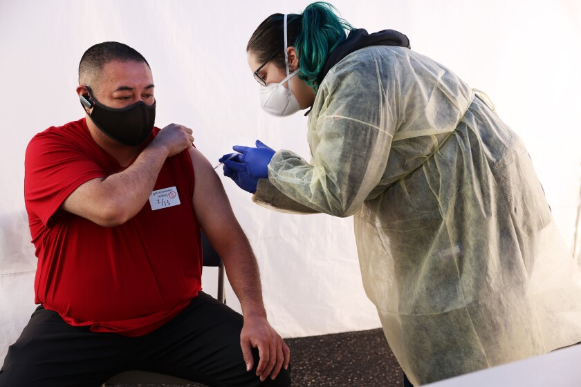 A healthcare worker administers a shot.