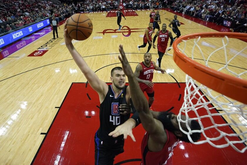 Clippers center Ivica Zubac (40) goes up for a shot as Rockets guard James Harden defends during the second half of a game March 5, 2020, in Houston.