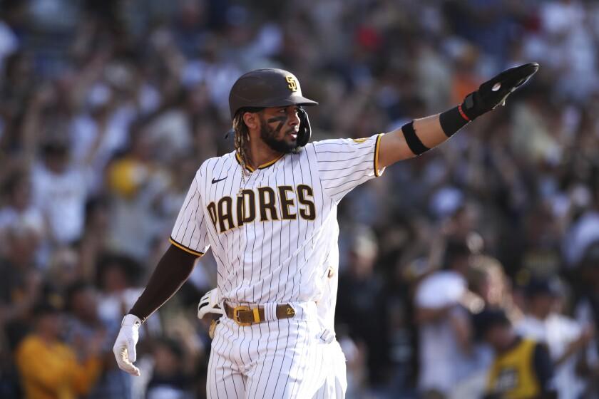 The Padres' Fernando Tatis Jr. points toward second base