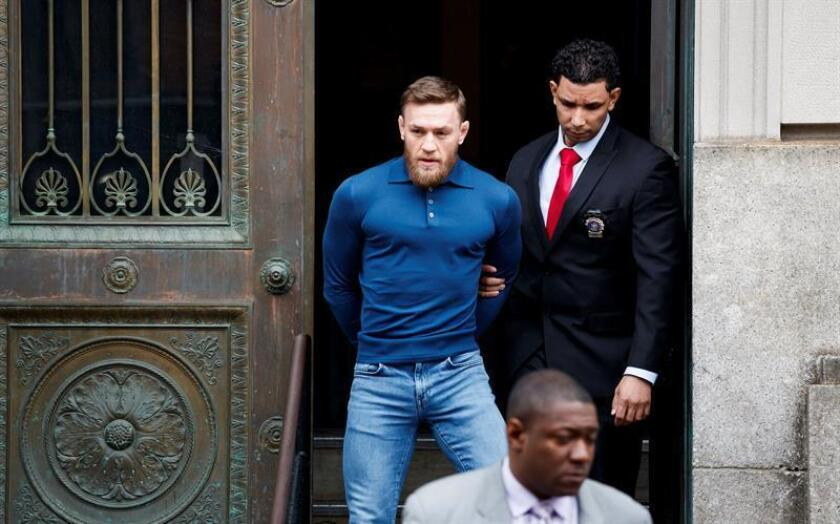 El luchador de artes marciales mixtas, el irlandés Conor McGregor (i), es escoltado mientars abandona una comisaria neoyorquina, en Estados Unidos, hoy, 6 de abril de 2018. EFE