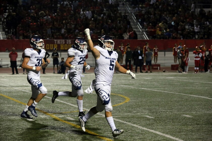 Newport Harbor's Johnny Brigandi celebrates with his teammates after recovering the ball during Newport Harbor's game against Woodbridge on Friday.