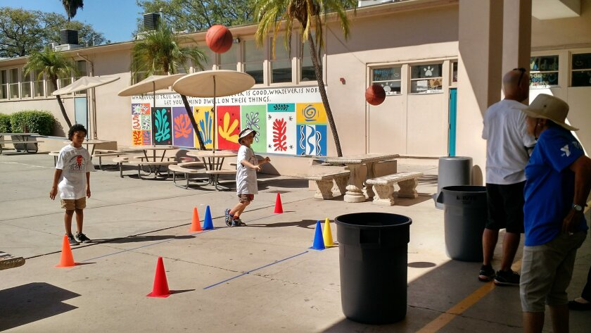 La Mesa Arts Academy students Julian Eubanks (left) and Parker Streit try their hand at basketball shooting at the Intergenerational Games held last Thursday at the school.