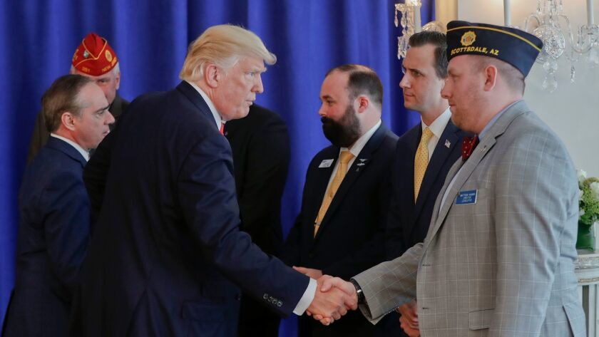 Veterans Affairs Secretary David Shulkin, left, and President Trump shake hands with military veterans after Trump signed the Veterans Affairs Choice and Quality Employment Act on Saturday in Bedminister, N.J.