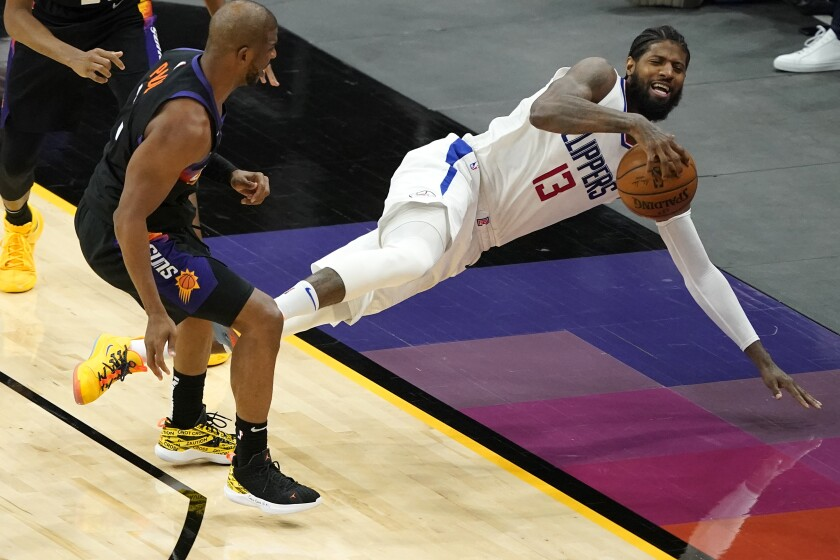 Clippers guard Paul George falls out of bounds after being fouled by Phoenix Suns guard Chris Paul.
