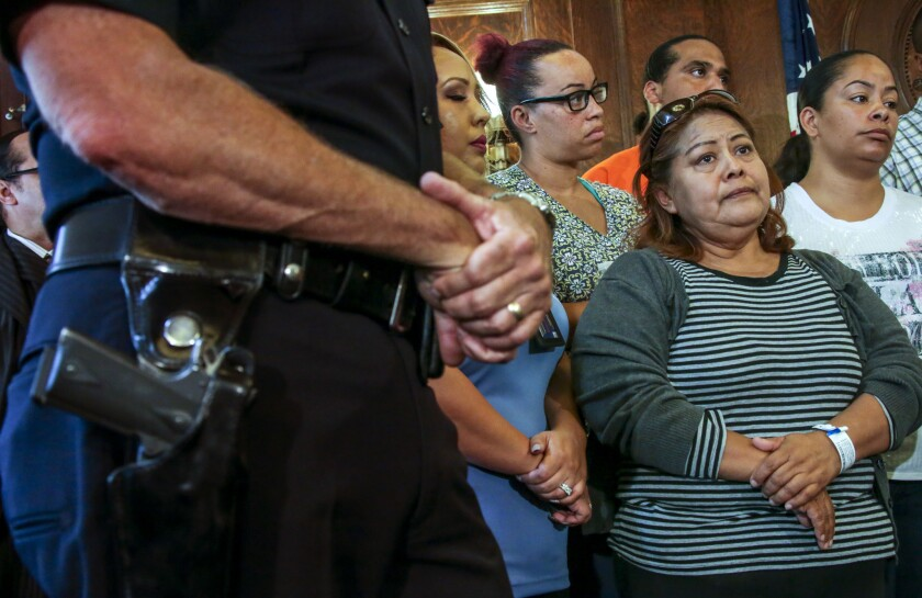 Francisca Xuncax, mother of a 13-year-old victim in a triple shooting in South L.A., listens to Mayor Eric Garcetti at a news conference.