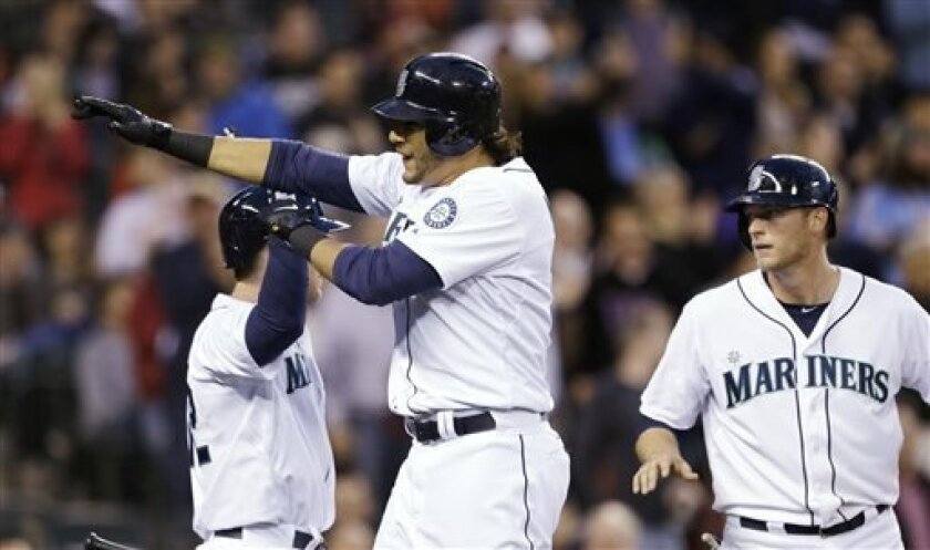 Seattle Mariners' Michael Morse, center, is congratulated by Jason Bay, left, and followed in by Michael Saunders on Morse's two-run him run against the Baltimore Orioles in the fourth inning of a baseball game Wednesday, May 1, 2013, in Seattle. (AP Photo/Elaine Thompson)