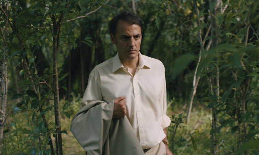 """A well-dressed man walks through a wooded area in the movie """"Azor."""""""