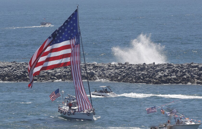 The Newport Harbor entrance on the 4th of July as huge waves crash at the Wedge.
