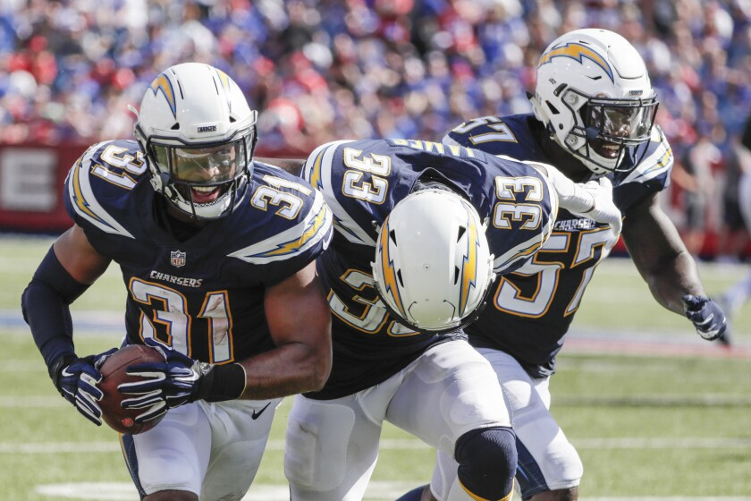 Chargers safety Adrian Phillips celebrates an interception with teammates Derwin James and Jatavis Brown at New Era Field on Sunday.